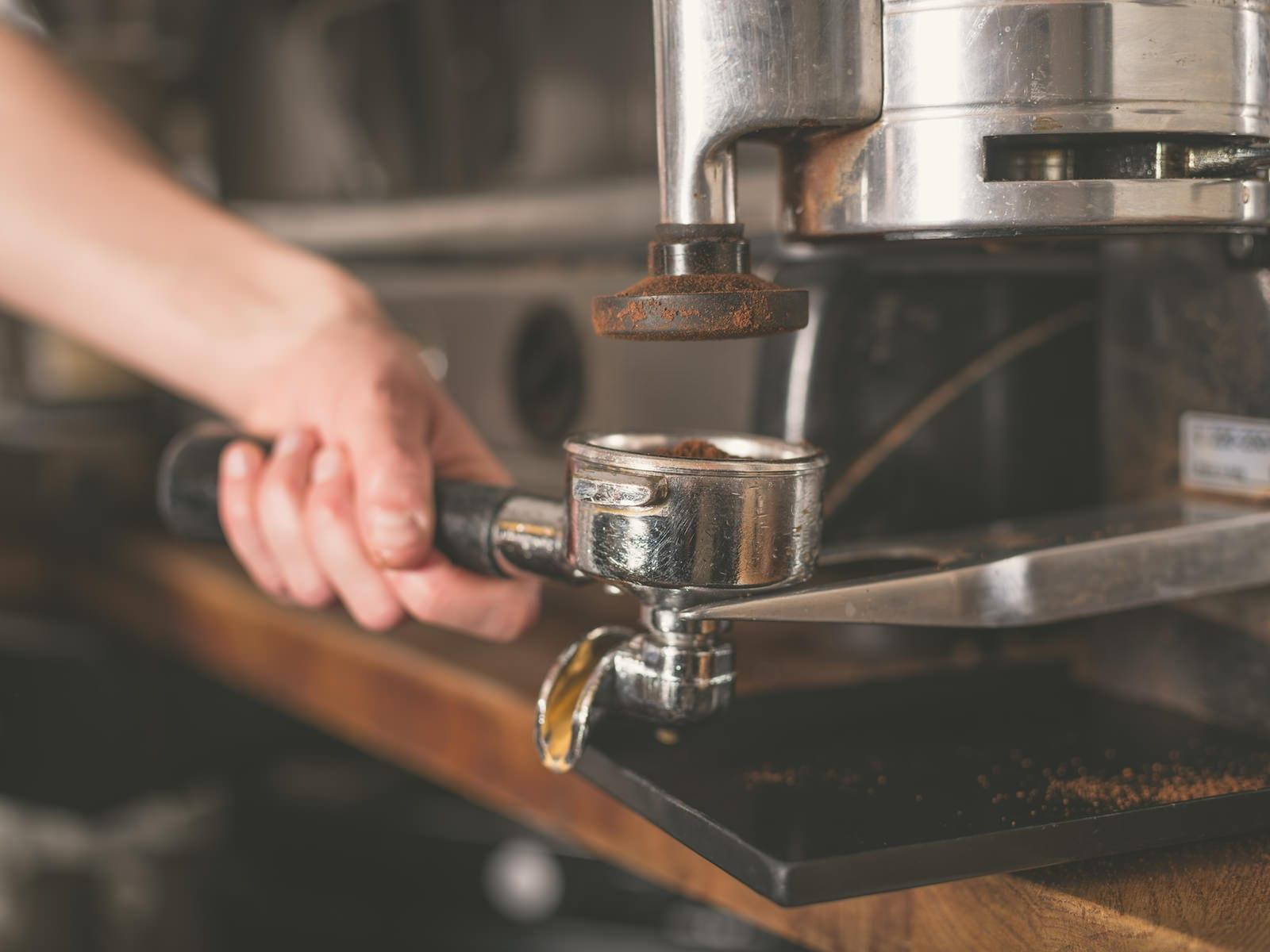 The hand of a young woman is operating a professional coffee machine